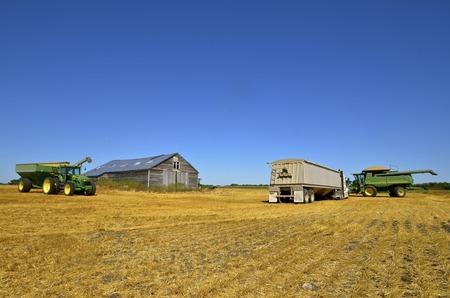 MAYVILLE, NOORD-DAKOTA-19 augustus 2015: Een oogstscène van een tractor en graanwagen, producten van John Deere Co, een Amerikaans bedrijf dat landbouw-, constructie-, bosbouwmachines en dieselmotoren produceert. Redactioneel