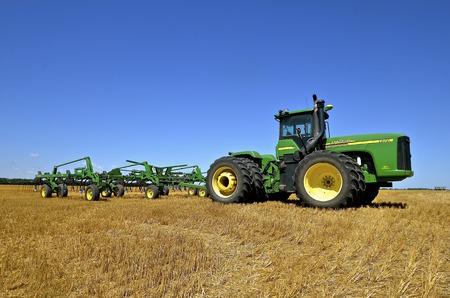 SABIN, MINNESOTA, 19 augustus 2015: Een John Deere tractor en digger geparkeerd in een geoogste tarwe veld zijn producten van John Deere Co, een Amerikaans bedrijf dat de landbouw, bouw, bosbouw, dieselmotoren en drivetrains fabriceert Redactioneel