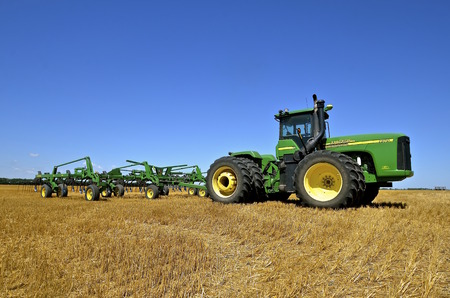 SABIN, MINNESOTA, August 19, 2015: A John Deere tractor and digger parked  in a harvested wheat field  are products of John Deere Co, an American corporation that manufactures agricultural, construction, forestry machinery, diesel engines, and drivetrains