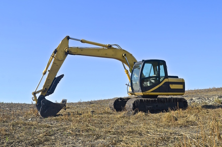 back hoe: A backhoe parked in a field is ready to dig trenches for tiling.
