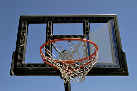 outdoor basketball court: The plexiglass of a backboard is broken on an outdoor basketball court.
