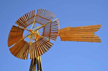 Vintage  farm windmill outlined against the deep blue sky Banco de Imagens