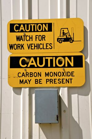 Signs posted on a warehouse door warn of moving lift forks and carbon monoxide gases. Фото со стока
