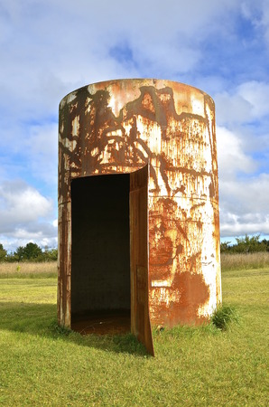 Metal cutter and welder has created a permanent welded open door on a rusty old huge oil tank.