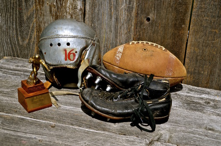 football shoes: An old leather football, shoes, helmet, and a trophy bring back memories of a past era of the gridiron.