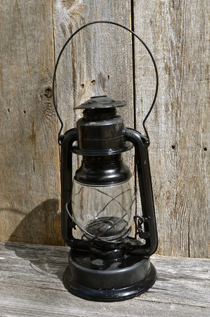 An old vintage lantern cast it's shadow on the weathered  barn wood it rests on. Imagens - 57084086