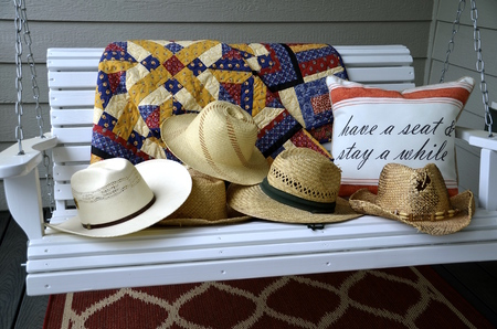 f60ca136 Classic vintage straw hats are staked on an outdoor porch swing. Stock Photo