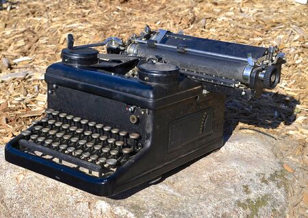typer: An old black carriage typewriter with a ribbon is pre-computer days