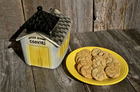 schoolhouse: Old vintage one room schoolhouse cookie jar with a plate of chocolate chip cookies Stock Photo