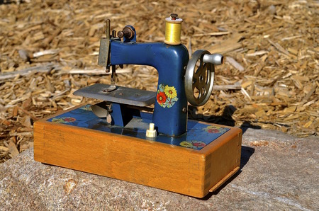 Anold mini-sewing machine in a wooden box Stock Photo