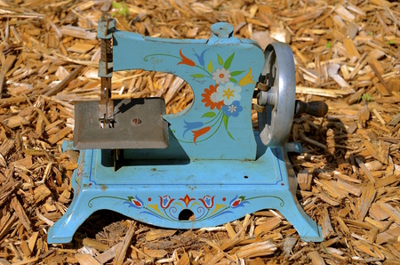 An old blue rosemalled  mini sewing machine