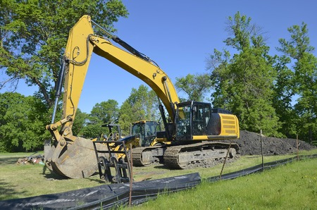 dirt pile: A large excavating machine(backhoe) is parked alongside a huge pile of dirt Stock Photo