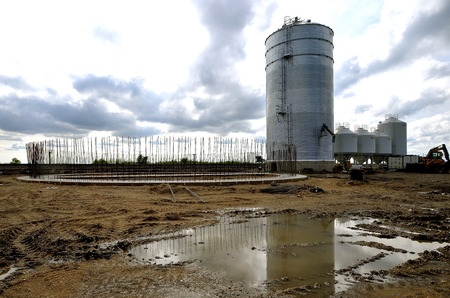 footing: The foundation of a new circular grain bin with reinforcing rods projecting upward after a thunderstorm.