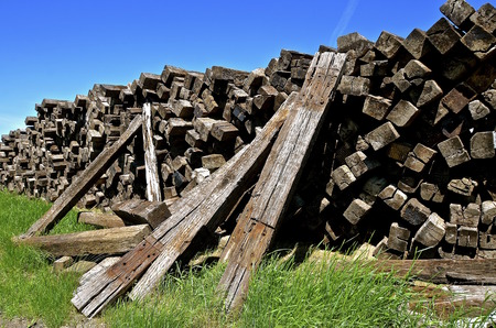 creosote: A  huge pile of stacked railroad ties have been removed from the track bed.