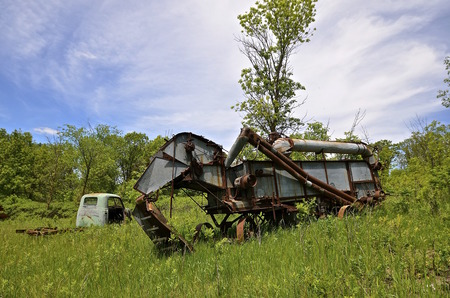 threshing: An old threshing machine and truck are left in a grassy meadow.