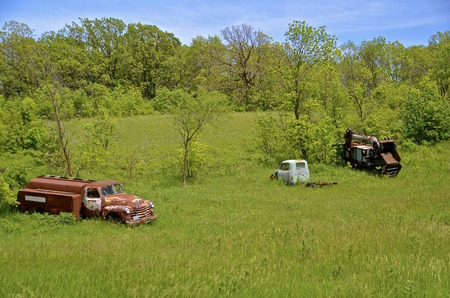 Parked on an edge of a woods is an old threshing machine, a fuel truck and a one ton pickup. Stock Photo