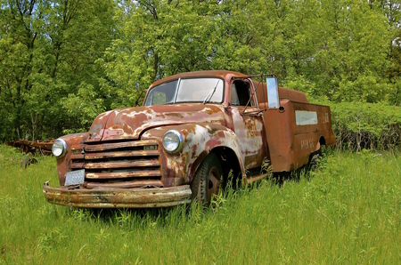 An old rusty 50s dilapidated fuel delivery truck is parked out in a field.