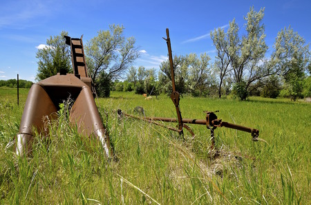 An old rusty one row corn picker  operated by power takeoff is left alongside a barbed wire fence in the long grass