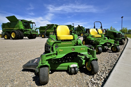 combines: MOORHEAD, MINNESOTA, June 6, 2016: The new combines and riding lawn mowers are products of John Deere Co, an American corporation that manufactures agricultural, construction, forestry machinery, diesel engines, and drivetrains.