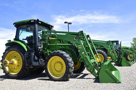 john deere: MOORHEAD, MINNESOTA, June 6, 2016: The new diesel tractors and front end loaders are products of John Deere Co, an American corporation that manufactures agricultural, construction, forestry machinery, diesel engines, and drivetrains. Editorial