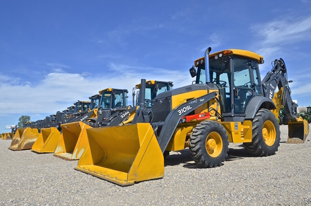 john deere: MOORHEAD, MINNESOTA, June 6, 2016: The new backhoe and front end excavator machines  are products of John Deere Co, an American corporation that manufactures agricultural, construction, forestry machinery, diesel engines, and drivetrains. Editorial