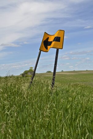 grassy: A crumpled  road sign in a grassy field indicates a curve in the road which appears illusive. Stock Photo