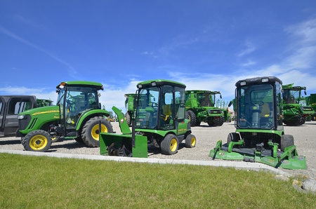 john deere: MOORHEAD, MINNESOTA, June 6, 2016: The new diesel tractor, combines, lawn tractor, and snow blower are products of John Deere Co, an American corporation that manufactures agricultural, construction, forestry machinery, diesel engines, and drivetrains.