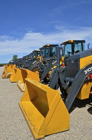 machinery: MOORHEAD, MINNESOTA, June 6, 2016: The new backhoe and front end excavator machines  are products of John Deere Co, an American corporation that manufactures agricultural, construction, forestry machinery, diesel engines, and drivetrains. Editorial