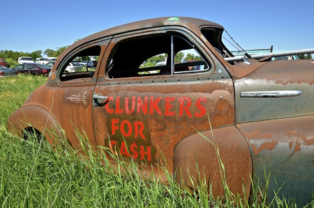 An old rusty car in a junkyard is used as an advertisement of paying cash for clunkers Stock Photo