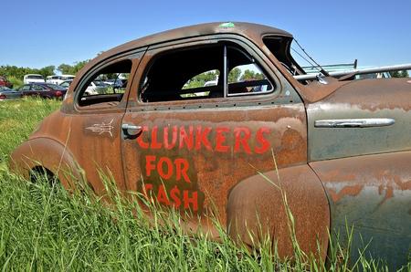 Een oude roestige auto in een autokerkhof wordt gebruikt als een reclame van het betalen contant geld voor clunkers Stockfoto