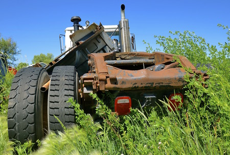 A semi cab is missing the right wheels after a collision and is left in a junkyard. Stock Photo