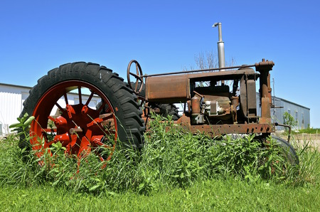 An old rusty tractor stands in long grass and weeds and has a painted red wheel.