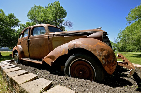 Old rusty wrecked car of the 40s serves as a lawn ornament Stock Photo