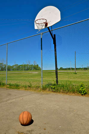 Basketball left on an outdoor court in a rural setting