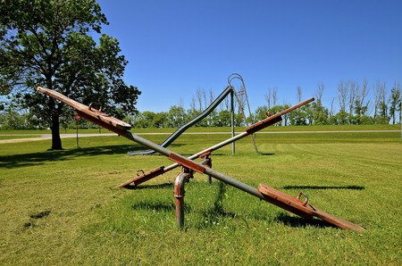 teeter: An old styled pair of teeter totters and an old metal slippery slide are located in a city park of a small rural town.