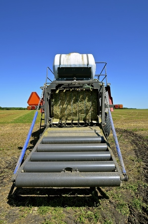 baler: The back of a modern square hay baler where the bale travels down the rollers to meet earth.