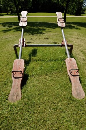 teeter: An old styled pair of teeter totters  are located in a city park of a small rural town. Stock Photo