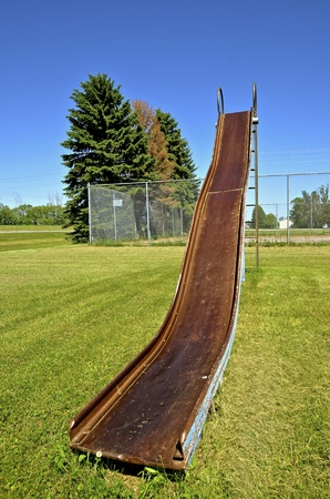 rural town: An old  rusty metal slippery slide is located in a city park of a small rural town. Stock Photo