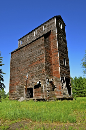 constructed: A deteriorating old elevator constructed with wood stands empty, falling into ruins, and leaving memories of a past era Stock Photo