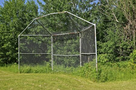 An old baseball backstop sets by itself along a tree line Stock Photo - 60767754