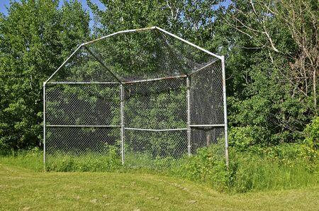 backstop: An old baseball backstop sets by itself along a tree line