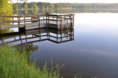 extending: An extending dock casts its reflection upon the smooth tranquil water of a lake