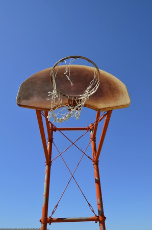 backboard: An outdoor basketball backboard is full of rust and holds a ripped net.