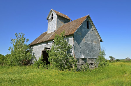 An abandoned small granary or elevator with an open door is surrounded by volunteer bushes.