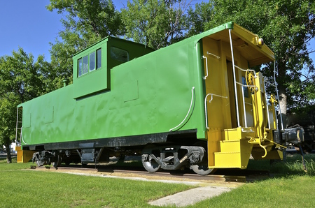 caboose: Vintage green caboose with  yellow steps leading to the back door. Stock Photo