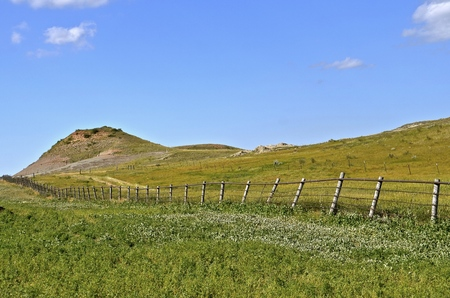 Fenced ranch land leading to a butte in the Badlands of North Dakota