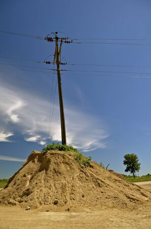 utility pole: Remains of a huge sand pile remain, surrounding a utility pole