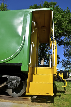 Save Download Preview Vintage green caboose with yellow steps leading to the back door.