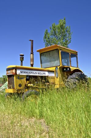 company merger: BARNESVILLE, MINNESOTA, JUNE 15, 2016: Parked in the long grass is an old  Minneapolis Moline tractor, a company based in Minnesota, and was the product of a merger between three companies in 1929: Minneapolis Steel & Machinery (MSM), Minneapolis Thresher Editorial