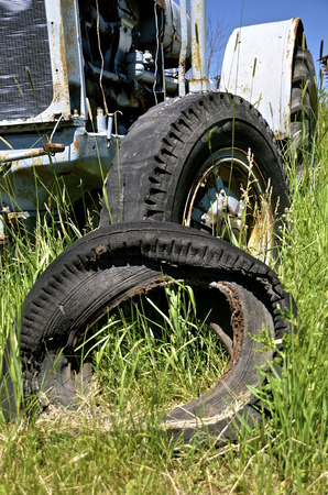 tyre tread: A rotten worn-out tire lies in front of a very old tractor Stock Photo